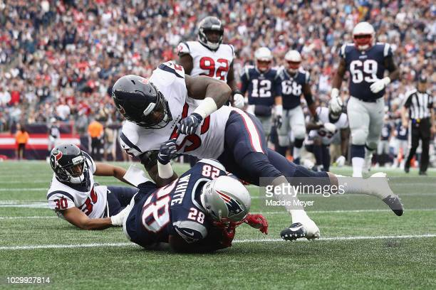 Benardrick McKinney of the Houston Texans tackles James White of the New England Patriots as he scores a touchdown during the second quarter at...