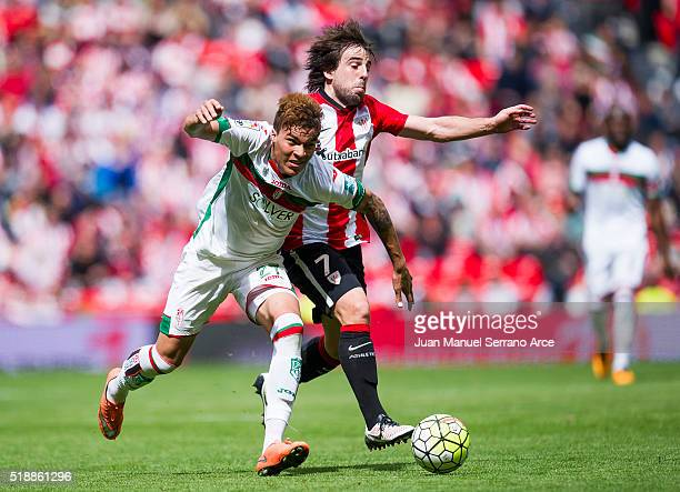 Benat Etxebarria of Athletic Club Bilbao competes for the ball with Adalberto Penaranda of Granada CF during the La Liga match between Athletic Club...