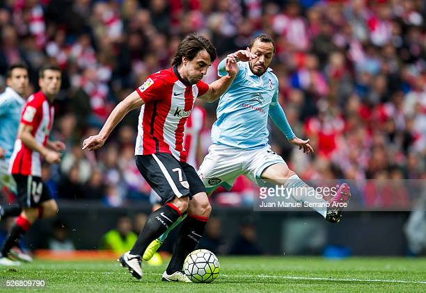 Benat Etxebarria of Athletic Club Bilbao competes for the ball with Marcelo Diaz of RC Celta de Vigo during the La Liga match between Athletic Club...