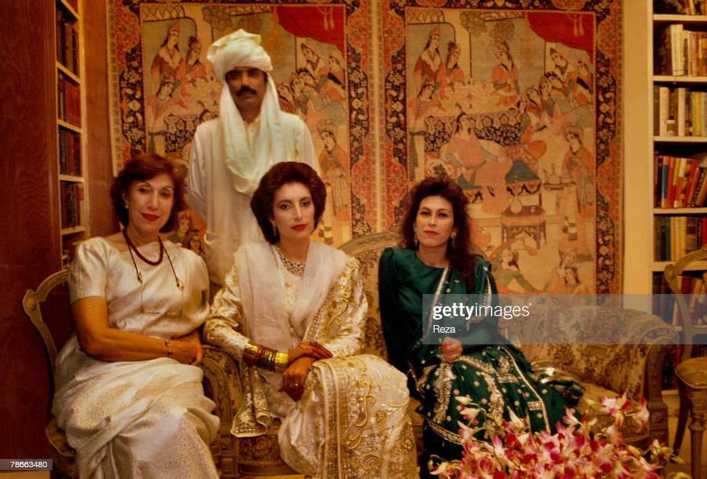 Benazir Bhutto (center), her mother, Nusrat Bhutto (left), Benazir's sister Nassim (right) and Benazir's husband, Asif Zardari on their December 18, 1987, at the Clifton Palace garden in Karachi, Pakistan. Benazir broke with tradition by trying to keep their wedding simple. She eliminated the dowry, had only two shalwar kameez instead of the traditional nearly 51 dresses and wore only one layer of jewelry. Benazir wore a white silk tunic with gold-embroidery. Asif wore a turban and a cream-colored tunic. Asif and Benazir and their families had several days of celebration. The couple said 'yes' three times, and at their wedding ceremony Benazir and Asif looked into a mirror together so they could see themselves as a married couple for the first time. Sugar was ground over their heads so their lives would be sweet. In the streets after their wedding there were 100,000 political supporters dancing, singing, firing guns in the air, and enjoying fireworks.