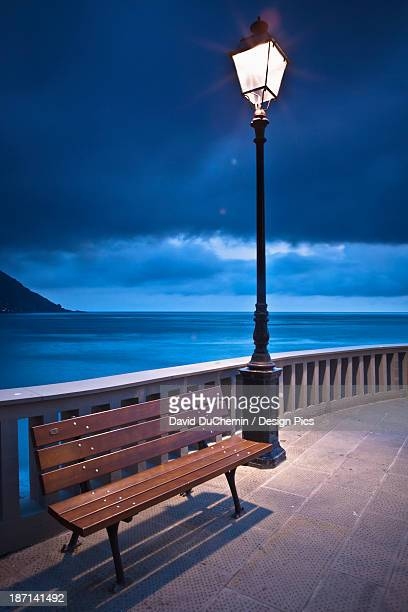 A Bench And Light Post Along The Railing On The Coast