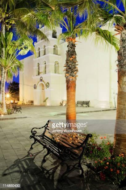 bench and palm trees near mision nuestra senora del pilar - todos santos mexico fotografías e imágenes de stock