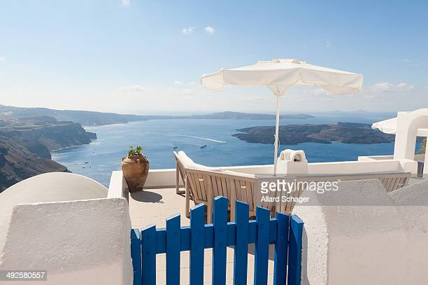 CONTENT] Bench and parasols on terrace overlooking Caldera and Aegean Sea Santorini Greece