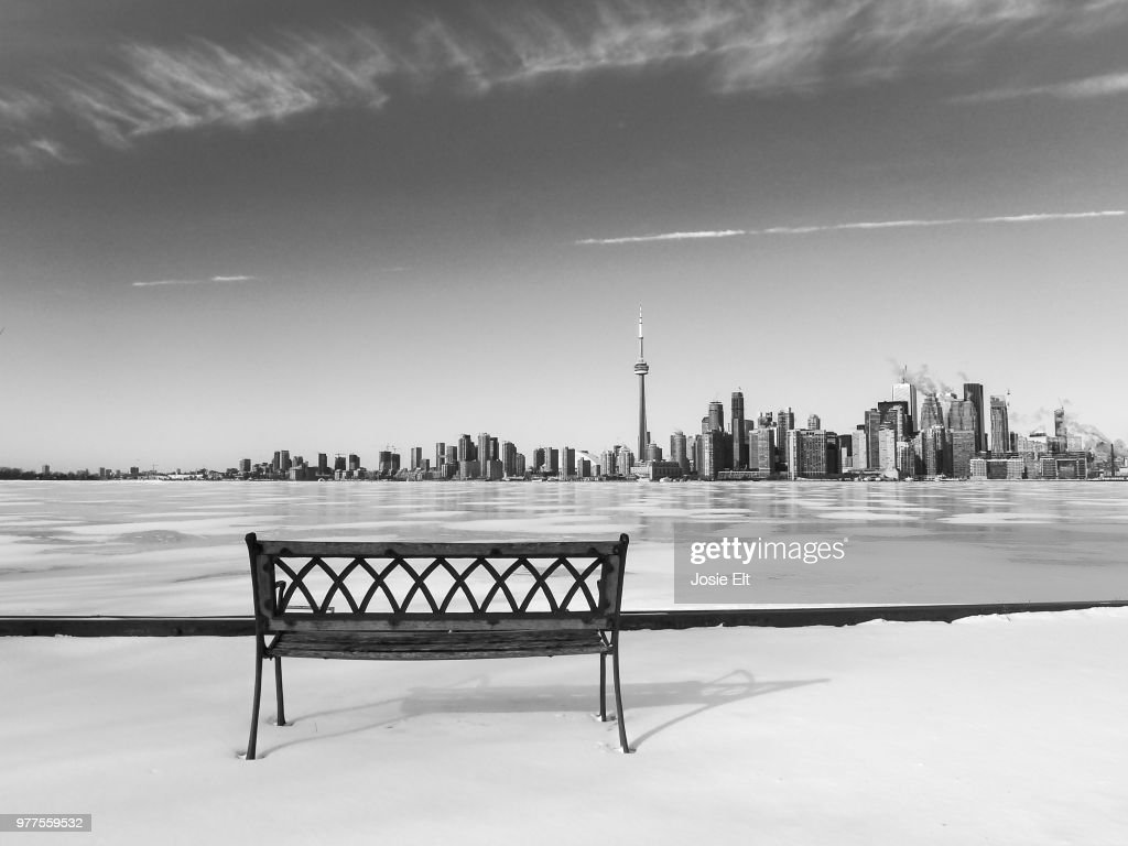 Bench By Frozen Lake Against City Panorama Toronto Ontario Canada