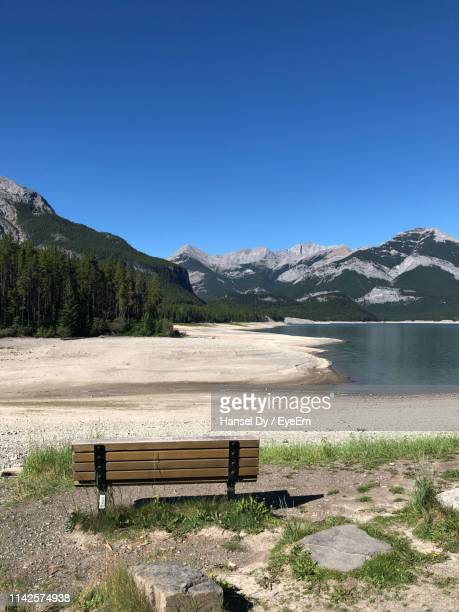 bench by lake against clear blue sky - kananaskis country stock pictures, royalty-free photos & images
