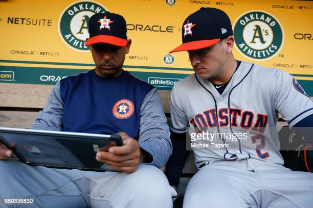 Bench Coach Alex Cora and Alex Bregman of the Houston Astros work in the dugout prior to the game against the Oakland Athletics at the Oakland...
