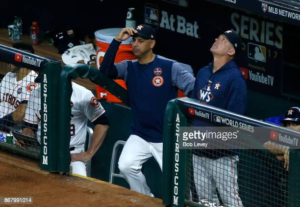 Bench coach Alex Cora and manager AJ Hinch of the Houston Astros look on from the dugout during the fifth inning against the Los Angeles Dodgers in...