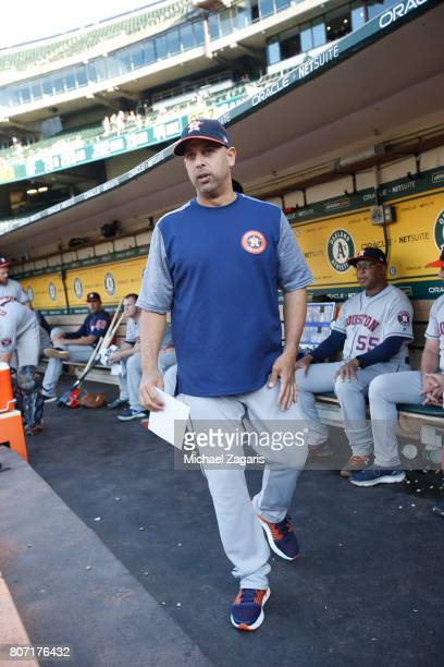 Bench Coach Alex Cora of the Houston Astros stands in the dugout prior to the game against the Oakland Athletics at the Oakland Alameda Coliseum on...