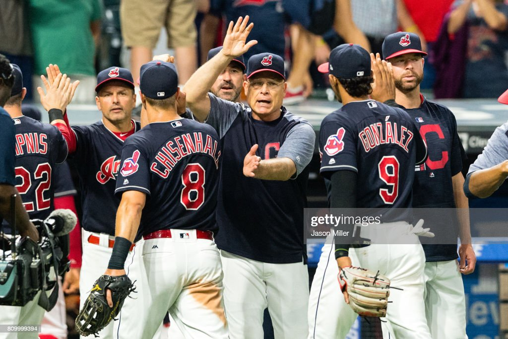 Bench coach Brad Mills celebrates with Lonnie Chisenhall #8 and Erik Gonzalez #9 of the Cleveland Indians after the Indians defeated the San Diego Padres at Progressive Field on JULY 6, 2017 in Cleveland, Ohio. The Indians defeated the Padres 9-2.