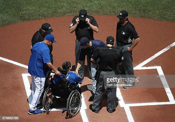 Bench coach DeMarlo Hale of the Toronto Blue Jays brings out the lineup card to the umpires as he wheels out Matthew of the MakeAWish Foundation with...