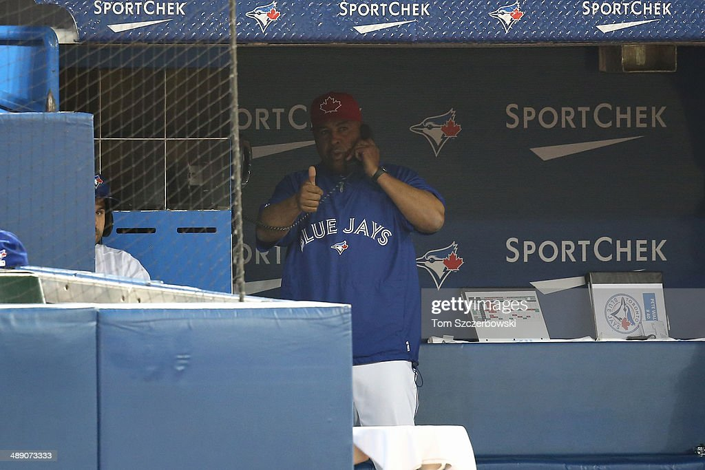 Bench coach DeMarlo Hale #20 of the Toronto Blue Jays signals his go-ahead to manager John Gibbons #5 from the dugout to challenge a play at home plate in the fifth inning during MLB game action against the Los Angeles Angels of Anaheim on May 9, 2014 at Rogers Centre in Toronto, Ontario, Canada.