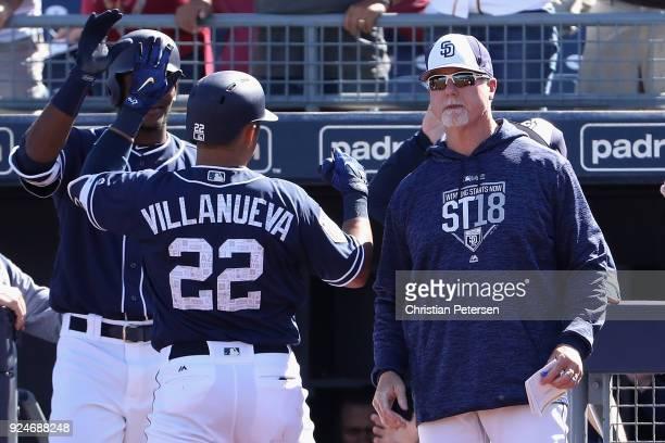 Bench coach Mark McGwire of the San Diego Padres congratulates Christian Villanueva after Villanueva hit a solo home run against the Los Angeles...