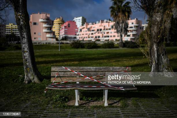 Bench covered with tape is pictured at Parque Tejo in Lisbon on January 22, 2021. - Portugal has closed schools for two weeks in a bid to contain a...