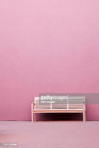 bench in front of pink wall - image en couleur photos et images de collection