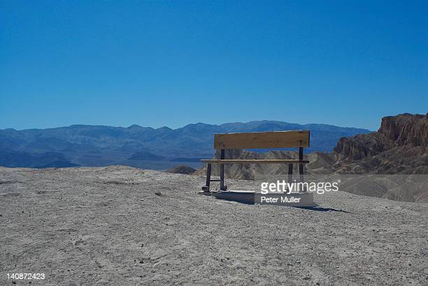 Bench on dirt path in mountains