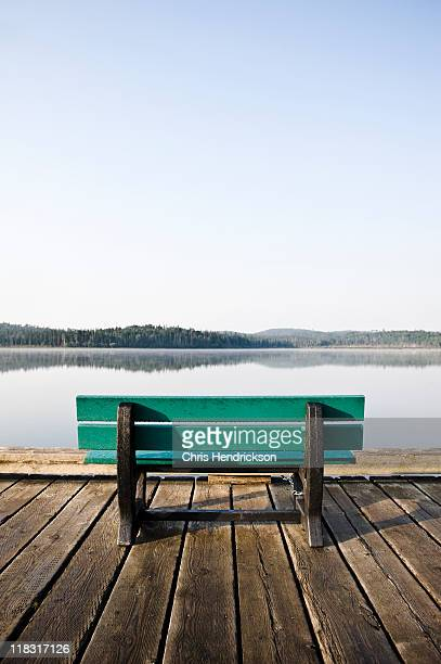 Bench on dock on a lake.
