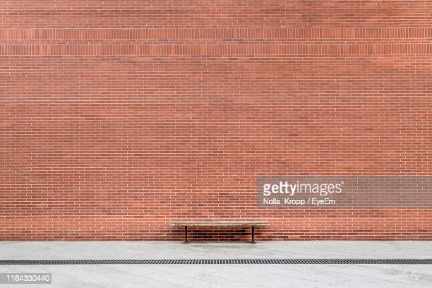 bench on footpath by brick wall - brick wall stock pictures, royalty-free photos & images