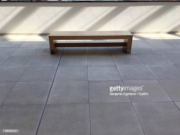 Bench On Pavement By Wall