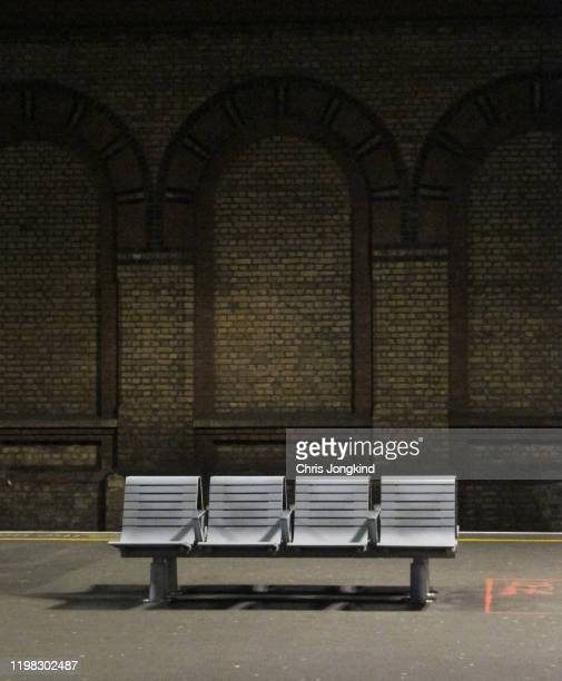 bench on platform against brick wall - bench stock pictures, royalty-free photos & images