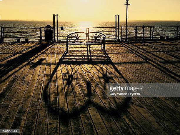 bench on wooden sidewalk by sea against sky at sunset - southend on sea stock pictures, royalty-free photos & images