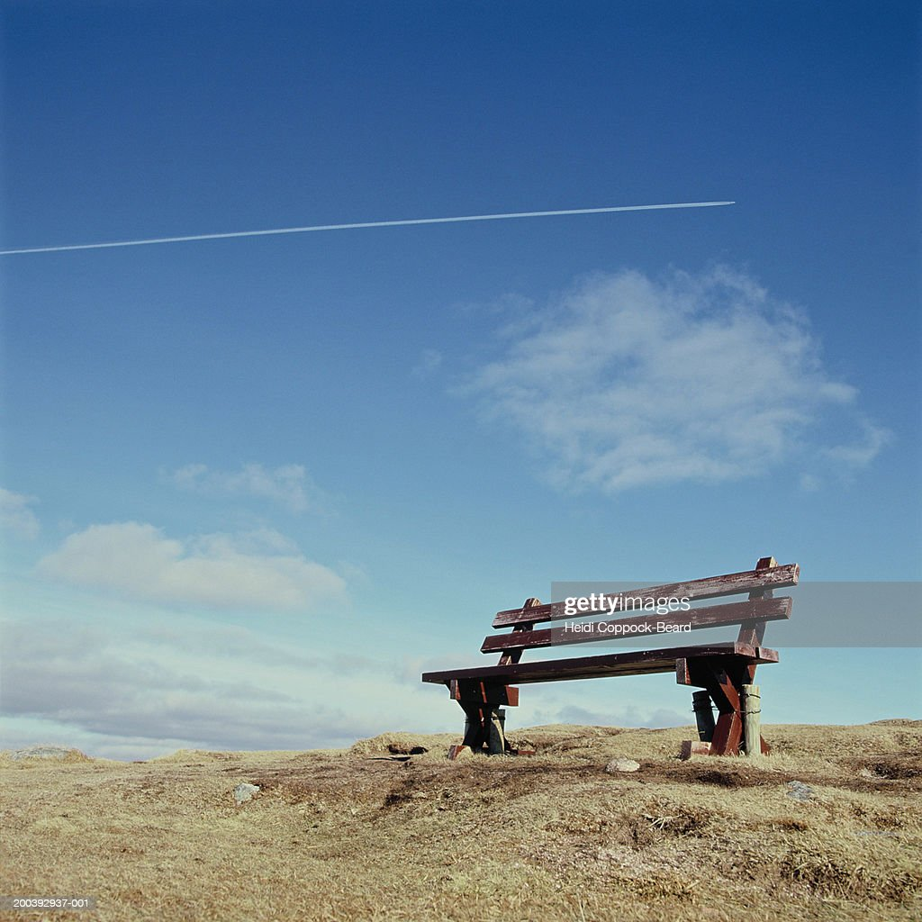 Bench with airplane trail in sky : Stock Photo