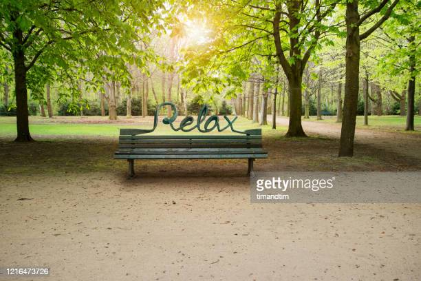bench with the word relax in a public park - resting stock pictures, royalty-free photos & images