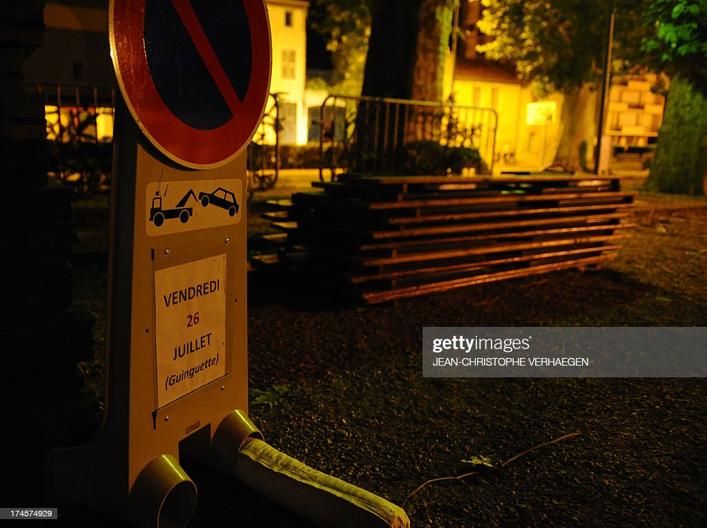 Benches are piled beside road sign reads 'Friday, July 26th (Open-air dance hall)' on July 28, 2013 in Joinville, Haute-Marne, eastern France on a place hit by a violent storm which collapsed on the audience during the evening, injuring three people very seriously and 27 lightly.