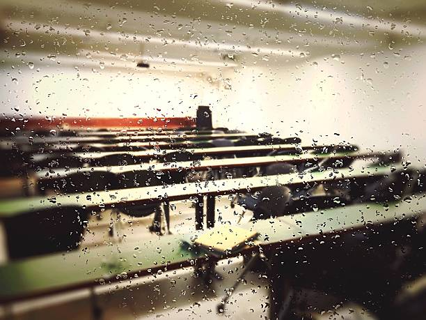 Benches in classroom seen through wet window