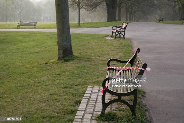 benches in park taped off during the corona virus lockdown. - london england stock pictures, royalty-free photos & images