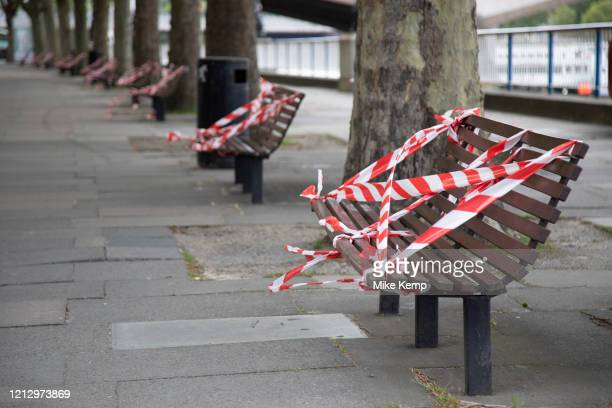 Benches on the South Bank are taped off to prevent people sitting down and so to preserve social distancing as lockdown continues and people observe...