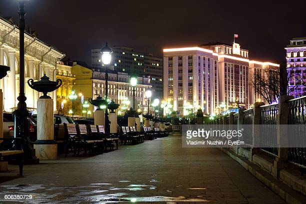 benches on walkway at park against illuminated buildings - rostov on don stock pictures, royalty-free photos & images