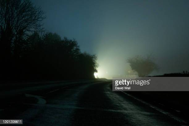 a bend on a country road, with a glowing light on the horizon. on a spooky misty winters night - back lit stock pictures, royalty-free photos & images