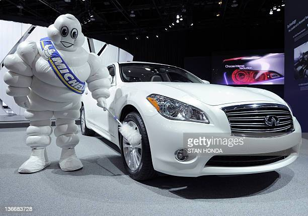 Bendo The Michelin Man dusts the tires on the Infiniti M56X during the press preview day at the 2012 North American International Auto Show January...