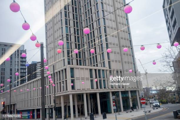 Beneath a high-rise of residential apartments, pink spherical lanterns hang from cables above the A11 in Stratford during the second wave of the...
