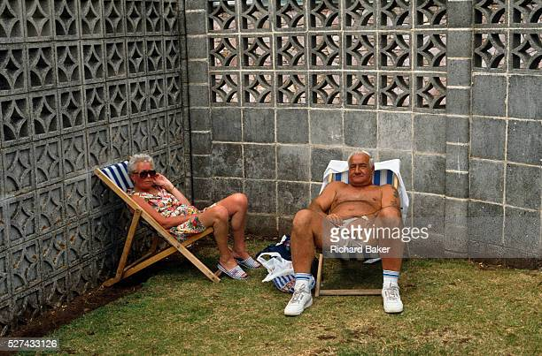 Beneath an ugly breeze block concrete wall a couple are enjoying their holiday in the English seaside town of Paignton Devon Sitting in striped...
