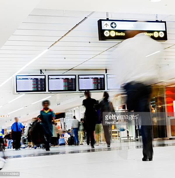 Beneath arrival/departure boards, people hurry through an airport