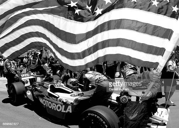 Beneath the fluttering Stars and Stripes flag of the United States, Michael Andretti is strapped aboard his Team Motorola Honda Lola before the start...