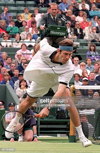 Beneath the gaze of the umpire Britain's Greg Rusedski rushes to the net to return the ball to his men's singles fourth round opponent Richey...