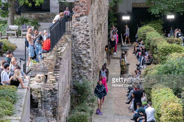Beneath the remains of London's Roman wall perimeter, models parade clothing styles during London fashio Week, on 21st September 2021, in the City of...