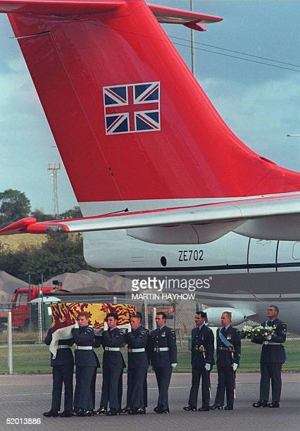 Beneath the Union Jack emblem on the tail of a Royal Squadron Aircraft of the RAF military pallbearers carry the casket containing the body of Diana...