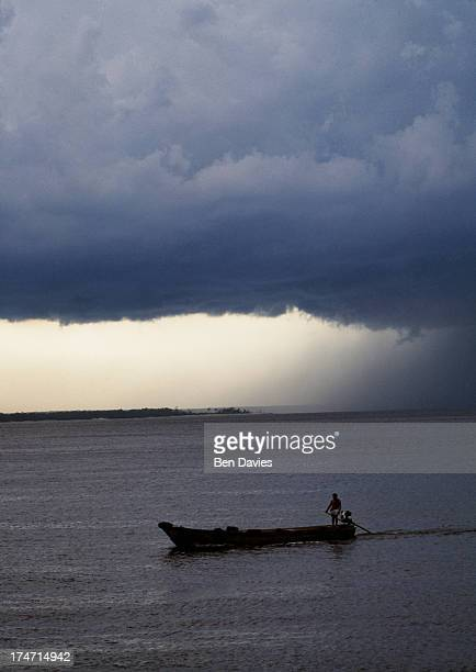 Beneath thick black rain clouds a boat steams down the Amazon River through the lush rain forest of Brazil near the town of Tefe The Amazon River in...