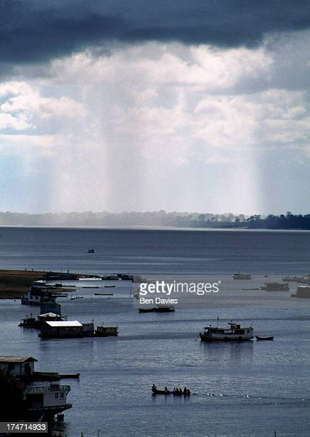 Beneath thick black rain clouds boats crisss cross the Amazon River through the lush rain forest of Brazil near the town of Tefe The Amazon River in...
