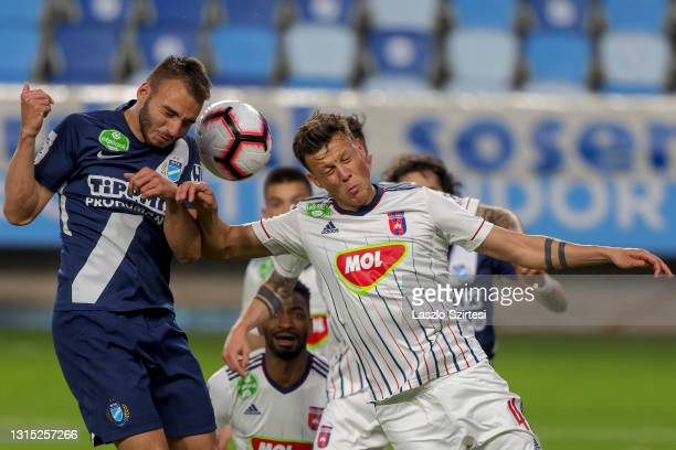 Benedek Varju of MTK Budapest battles for the ball in the air with Adrian Rus of MOL Fehervar FC during the Hungarian OTP Bank Liga match between MTK...