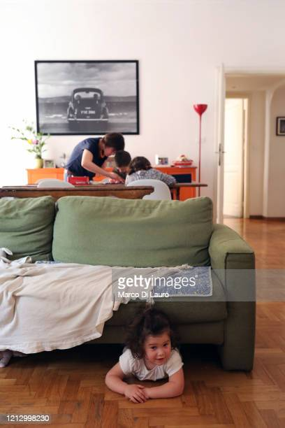 Benedetta attends to her two children as her other child hides under a sofa on May 13 2020 in Rome Italy The De Lazzaro family is composed of...