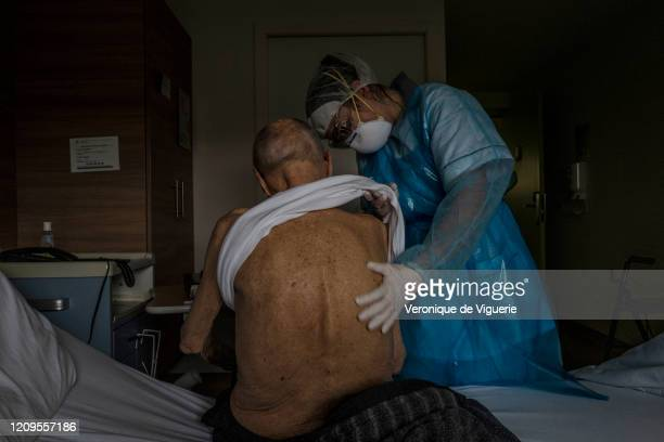 Benedicte, a healthcare worker, takes care of a coronavirus patient recovering at the Saint-Jean rehabilitation clinic on April 3, 2020 in Sentheim,...
