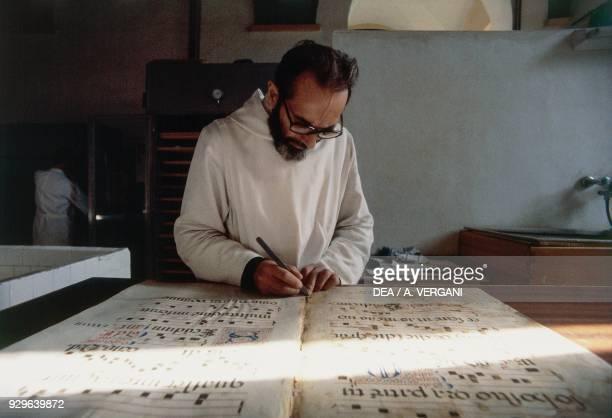 Benedictine monk restoring a manuscript, Abbey of Monte Oliveto Maggiore, Asciano, Tuscany, Italy.