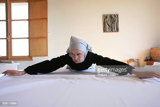benedictine nun making religious vestment - nun stock-fotos und bilder