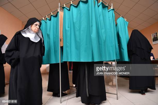 A Benedictine Sister of the SainteCécile Abbey exits a booth prior to casting her ballot during the first round of the legislative elections at a...