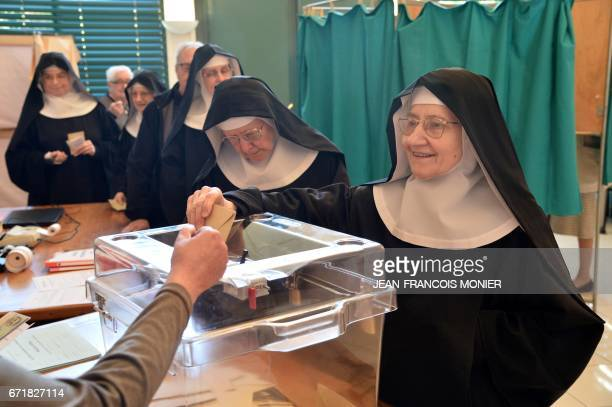 Benedictine sister of the SainteCecile Abbey casts her ballot at a polling station in Solesmes northwestern France during the first round of the...