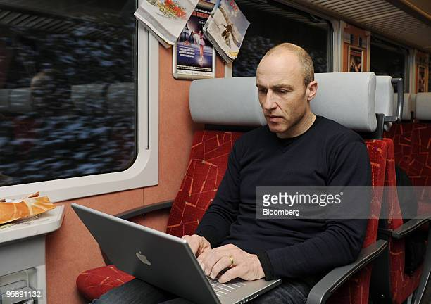Benedikt Germanier chief executive officer of ski company Zai AG works on an Apple MacBook computer while riding a train to his company's...